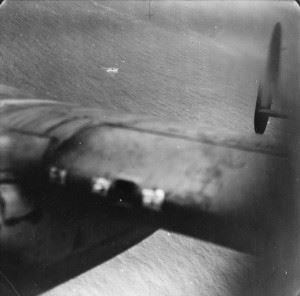 Photograph looking back over the starboard wing of a Lancaster of No 61 Squadron, Bomber Command, after an attack on U-751 in the Bay of Biscay, 17 July 1942. The U-boat had been attacked and crippled by a Whitley of No 502 Squadron earlier, before being finally sunk by depth charges dropped by the Lancaster.
