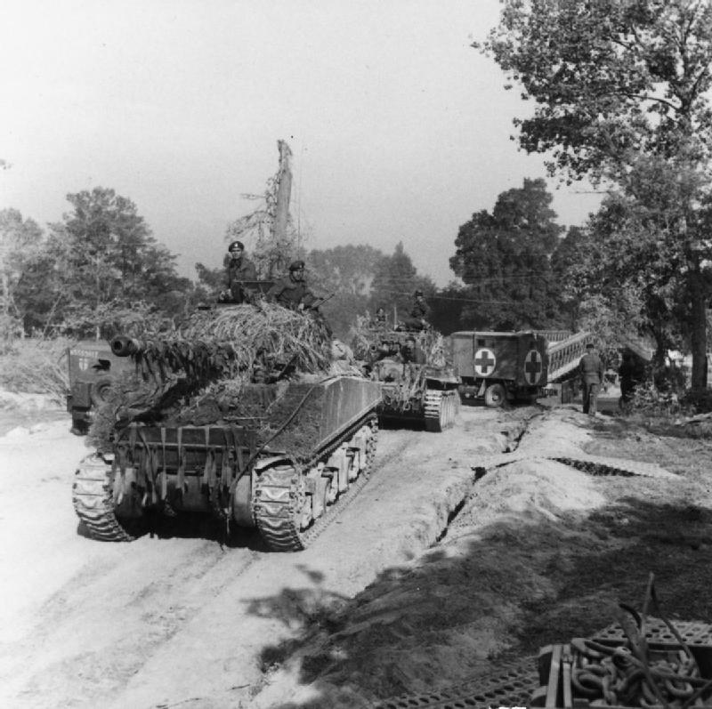 A heavily-camouflaged Sherman Firefly having just crossed a Bailey bridge over the Orne during Operation 'Goodwood', 18 July 1944.
