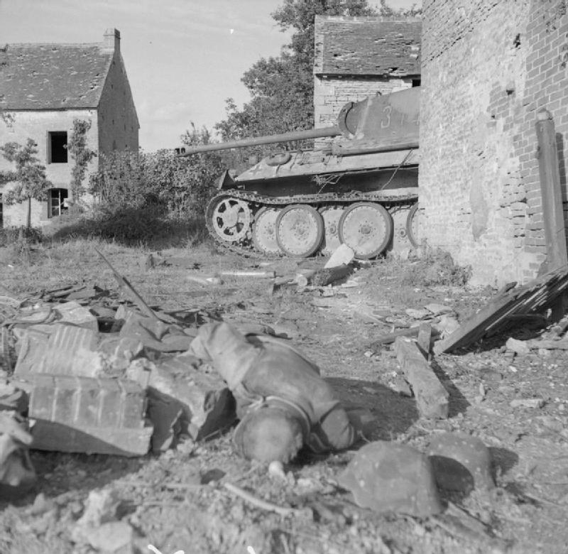 A knocked-out German Panther tank and a dead infantryman in the Falaise pocket, 25 August 1944.