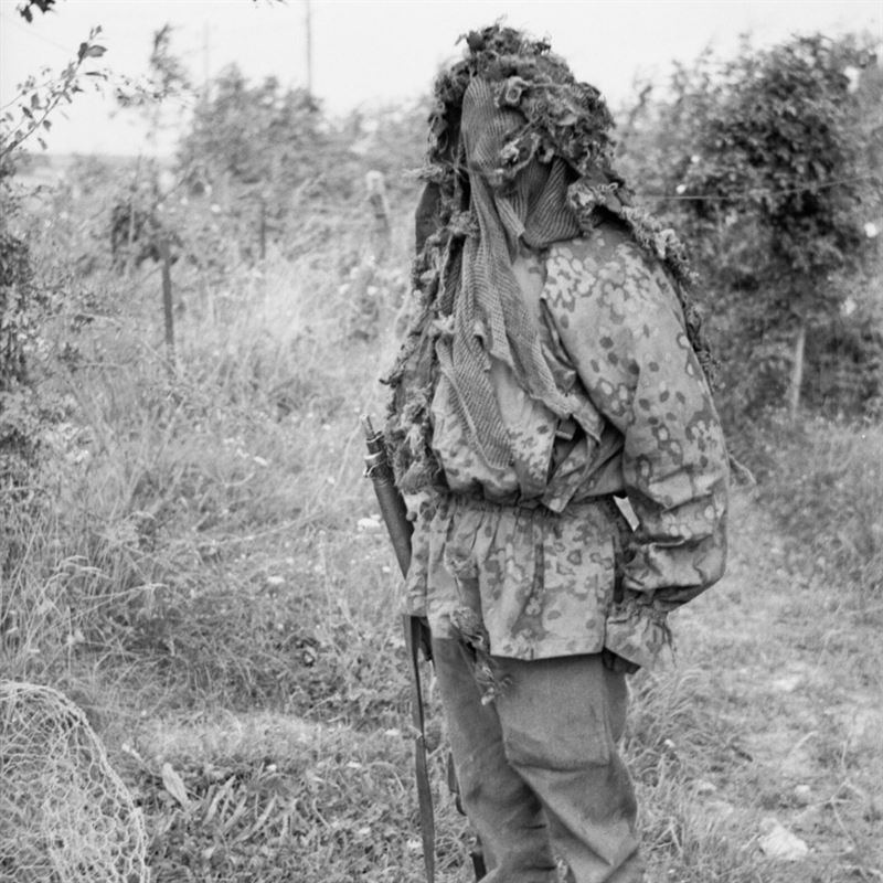 """A sniper demonstrates his camouflage (note: German Waffen-SS """"Dot"""" Pattern) at a sniper school in a French village, 27 July 1944."""