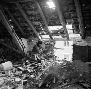 A sniper from C Company, 5th Battalion, The Black Watch , 51st (Highland) Division, in position in the loft space of a ruined building in Gennep, Holland, 14 February 1945.