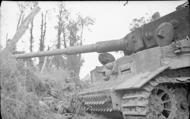 A soldier of 10th Durham Light Infantry digs in close to a knocked-out German Tiger tank at Rauray, 28 June 1944.