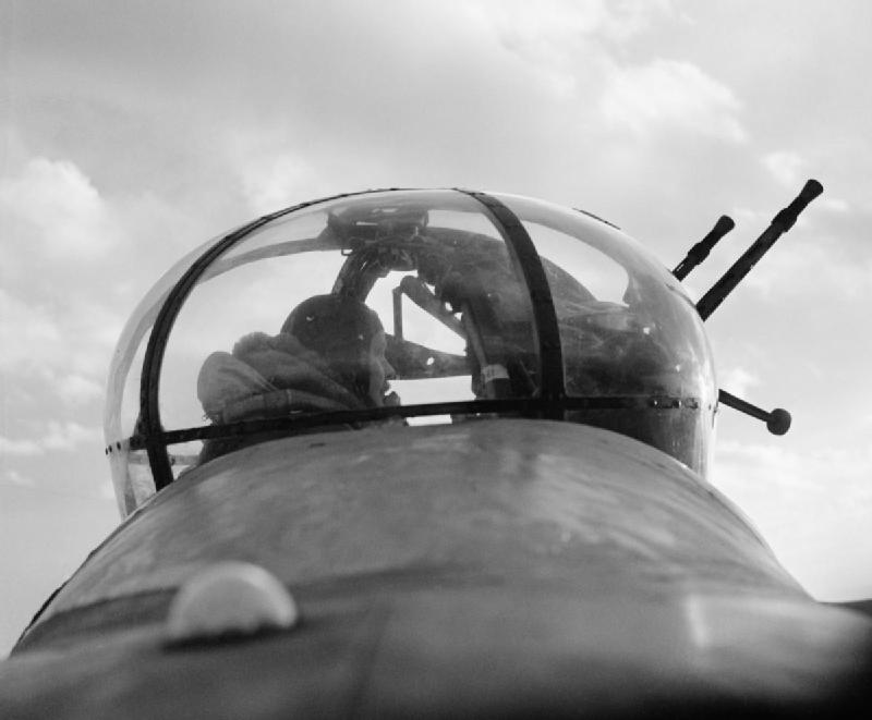 A No 57 Squadron mid-upper gunner, Sergeant 'Dusty' Miller, 'scans the sky for enemy aircraft' from a Lancaster's Fraser Nash FN50 turret. This image was part of a sequence taken for an Air Ministry picture story entitled 'T for Tommy Makes a Sortie', which portrayed the events surrounding a single Lancaster bomber and its crew during a typical operation.