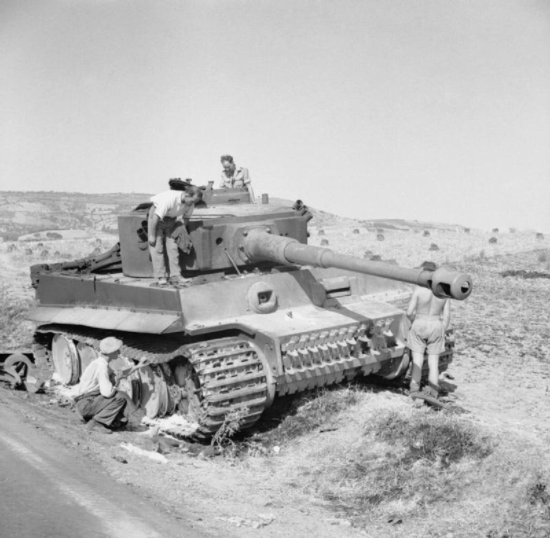 British troops and local civilians examine a knocked-out German PzKpfw VI Tiger tank, 19 July 1943.