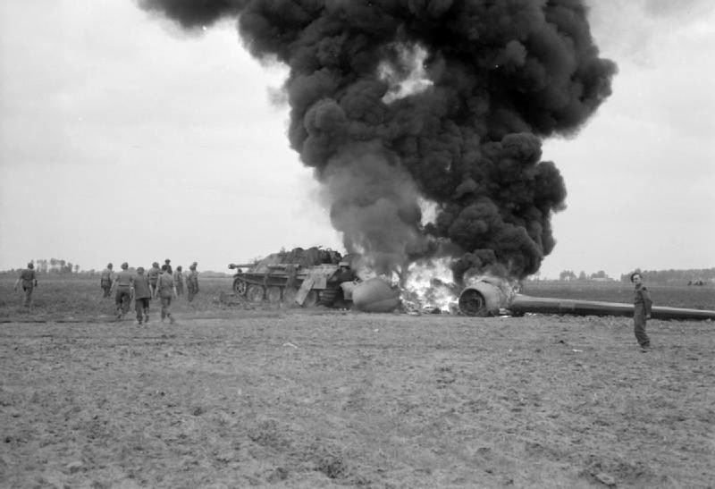 An USAAF C-47 aircraft, hit by flak returning from the Market-Garden drop, burns after crash-landing into a knocked-out German Jagdpanther in a field near Geel in Belgium.
