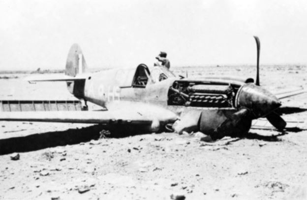 A German soldier near a crashed Curtiss Kittyhawk I fighter from No. 260 Squadron, Royal Air Force (squadron code A-HS), in North Africa.