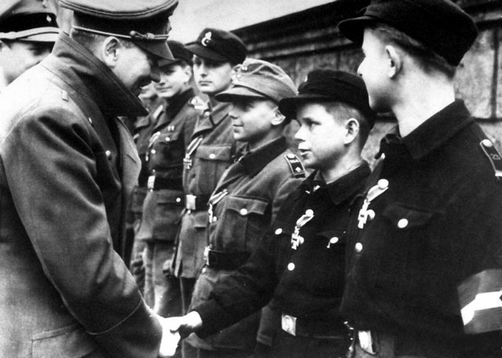 Adolf Hitler congratulates on 20 March 1945 the 12 year old Alfred Czech, left to Czech is WIlhelm Hübner.