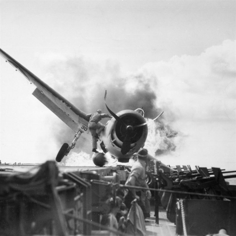 Crash landing of F6F-3, Number 30 of Fighting Squadron Two (VF-2), USS Enterprise, into the carrier's port side 20mm gun gallery, 10 November 1943. Lieutenant Walter L. Chewning, Jr., USNR, the Catapult Officer, is climbing up the plane's side to assist the pilot from the burning aircraft. The pilot, Ensign Byron M. Johnson, escaped without significant injury. Enterprise was then en route to support the Gilberts Operation. Note the plane's ruptured belly fuel tank.