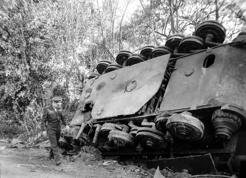 Gen. Dwight D. Eisenhower, supreme commander of the Allied expeditionary forces, inspects an overturned German tank left by a roadside in France by the retreating enemy