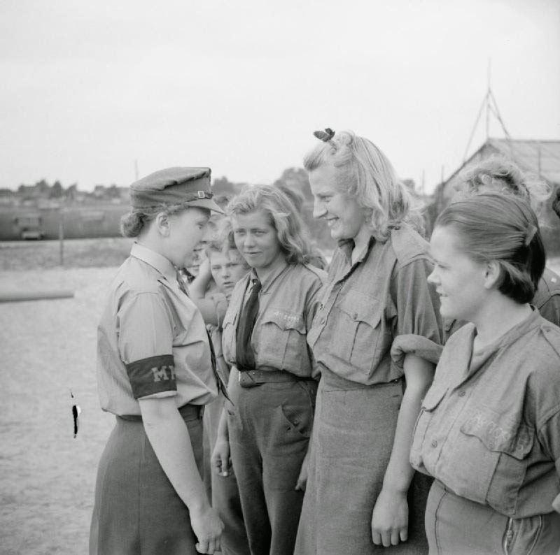 British Auxiliary Territorial Service Lance Corporal Jean Burck of New Malden, Surrey, England speaks to a group of female German POWs at Camp Vilvoorde. The camp was managed by British forces of the 21st Army Group and housed over 12,000 Axis POWs, both men and women. Vilvoorde, Flemish Brabant, Belgium. June 1945. Image taken by Lt. O'Brien, No. 5 Army Film & Photographic Unit.