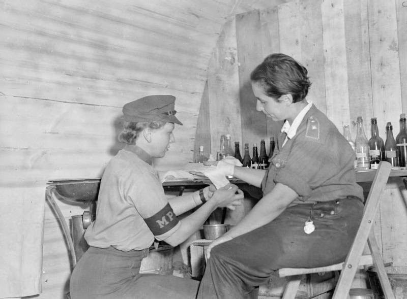 British Auxiliary Territorial Service Lance Corporal Jean Burck of New Malden, Surrey, England applies aid to Female LW German POWs at Camp Vilvoorde. The camp was managed by British forces of the 21st Army Group and housed over 12,000 Axis POWs, both men and women. Vilvoorde, Flemish Brabant, Belgium. June 1945. Image taken by Lt. O'Brien, No. 5 Army Film & Photographic Unit.