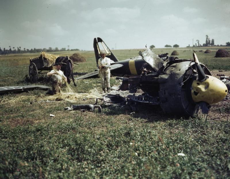 The wreckage of a Ju-88 purported to have been shot down by the Canadian Spitfires of Johnny Johnson's Wing lies not far from airstrip B-7 at Matragny, Normandy. The two French farmers are plaiting straw to bind clover bundles.