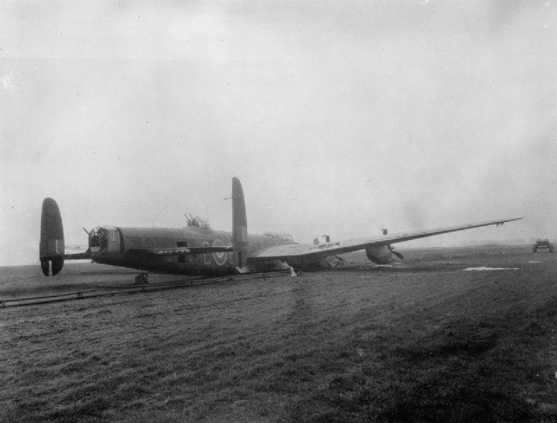 Avro Lancaster B Mark I, ME590 'SR-C', of No. 101 Squadron RAF, lies on the FIDO (Fog Investigation and Dispersal Operation) pipework at Ludford Magna, Lincolnshire, after a successful crash-landing on returning from a raid to Augsburg on the night of 25/26 February 1944.