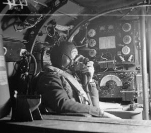 Flying Officer R W Stewart, a wireless operator on board an Avro Lancaster B Mark I of No. 57 Squadron RAF based at Scampton, Lincolnshire, speaking to the pilot from his position in front of the Marconi T1154/R1155 transmitter/receiver set.