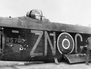 "The damaged fuselage and mid-upper turret of Avro Lancaster B Mark I, R5700 'ZN-G', of No. 106 Squadron RAF based at Elsham Wolds, Lincolnshire, after crash-landing at Hardwick, Norfolk, following an attack by a German fighter over Essen. R5700, was among 60 aircraft taking part in the first ""Oboe"" raid on Essen on the night of 13/14 January 1943, when it was twice attacked by a Focke Wulf Fw 190 ""Wilde Sau"" night-fighter shortly after bombing the target. The aircraft was severely damaged, the rear gunner was badly wounded and the mid-upper gunner, Sergeant J B Hood, was killed, but the pilot, Sergeant P N Reed, managed to fly the crippled bomber as far as the USAAF base at Hardwick before executing a successful crash-landing. Three weeks later, Sergeant Reed and his crew failed to return from a raid on Hamburg."