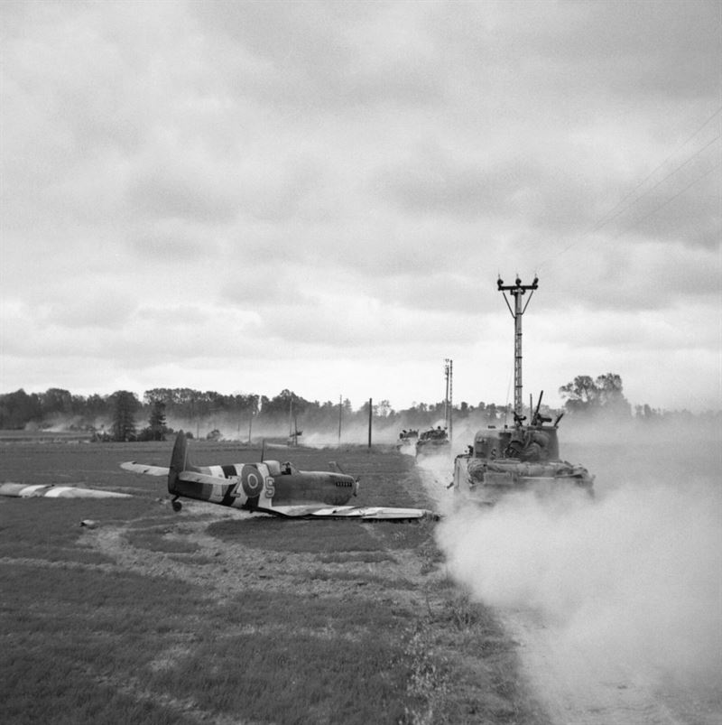 Sherman tanks move up past a crash-landed Spitfire, for an attack on Tilly-sur-Seulles, 17 June 1944. The Spitfire's squadron code – 'VZ' – indicates it belongs to RCAF 412 Squadron, which operated the Spitfire IXb during this period