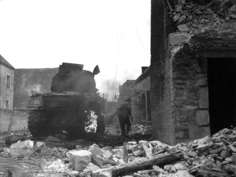 Soldier of Argyll & Sutherland Highlanders (4th Canadian Armoured Division) passing a destroyed Canadian tank in St. Lambert sur Dive