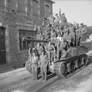 Tank crews crowd onto a Sherman Firefly to celebrate the capture of Le Beny Bocage, 1 August 1944.