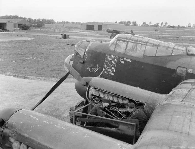 """Mechanics at work on an engine of Avro Lancaster B Mark III, LM577 'HA-Q' """"Edith"""", of No. 218 Squadron RAF on a pan hardstanding at Chedburgh, Suffolk."""