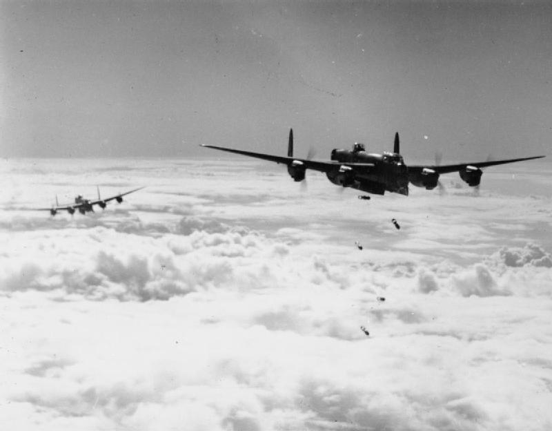 """An Avro Lancaster B Mark I or III of No. 514 Squadron RAF based at Waterbeach, Cambridgeshire, releases its bombs through cloud, during a daylight attack on a flying-bomb launch site at Les Catelliers in northern France, (""""Noball"""" Operation)."""
