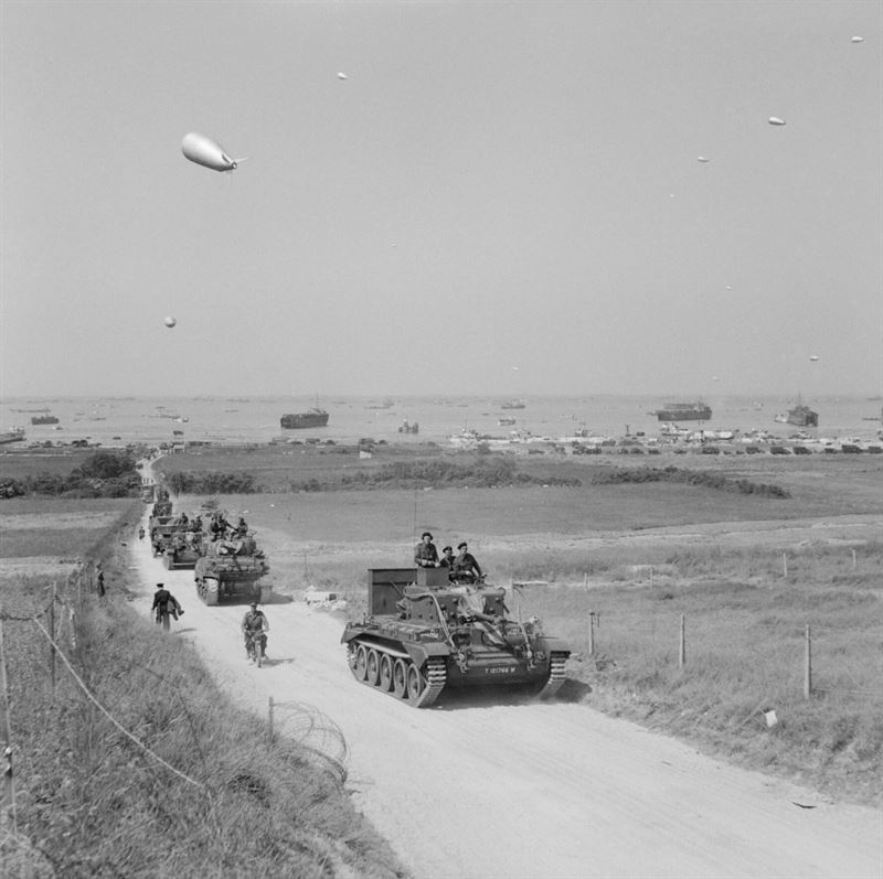 A Cromwell Mk V tank of 4th County of London Yeomanry, 22nd Armoured Brigade, 7th Armoured Division, leads a column of armour (including a Sherman Firefly immediately behind) and soft-skin vehicles inland from King beach, Gold area, 7 June 1944.