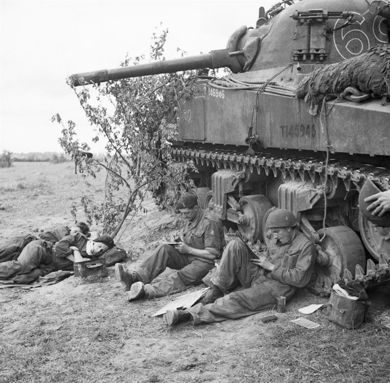 Sherman tank crew of 'C' Squadron, 13th/18th Royal Hussars, 27th Armoured Brigade, rest and write letters home by the side of their vehicle, 10 June 1944.