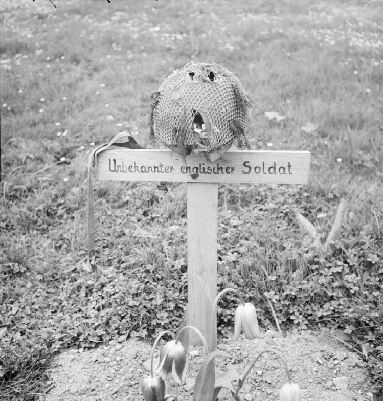 """The grave of a British airborne soldier killed during the battle of Arnhem in September 1944, photographed by liberating forces on 15 April 1945. On the cross is written in German """"Unknown British soldier""""."""
