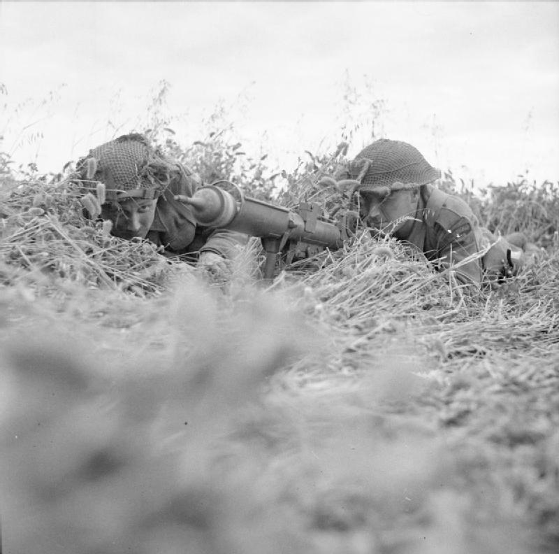 Rifleman Reg. Oates of Walthamstow and Sergeant James Woodward of Tottenham take up a position with a Piat mortar in a cornfield near Caen.