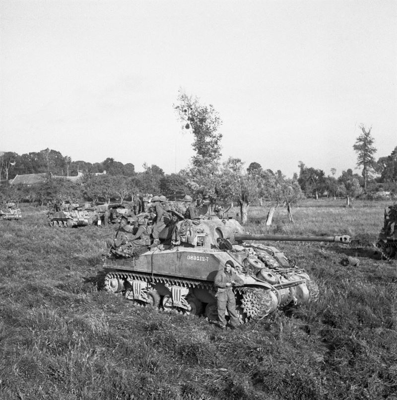 Infantry and Sherman tanks wait to advance at the start of Operation 'Goodwood', 18 July 1944. A Sherman Firefly is in the foreground.