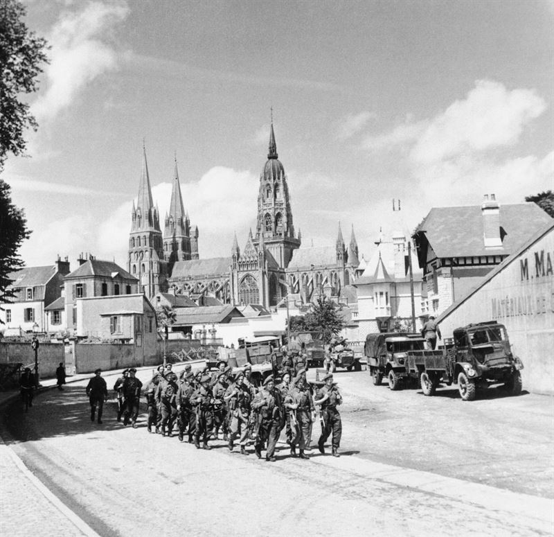 Troops marching through Bayeux, with the cathedral in the background, 27 June 1944.
