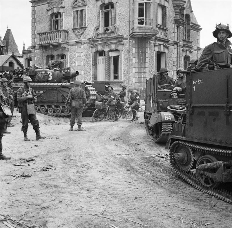 Universal Carriers of 2nd Middlesex Regiment (3rd Division's MG battalion) pass a Churchill AVRE of 77th Assault Squadron, 5th Assault Regiment, in La Brèche d'Hermanville, 6 June 1944.