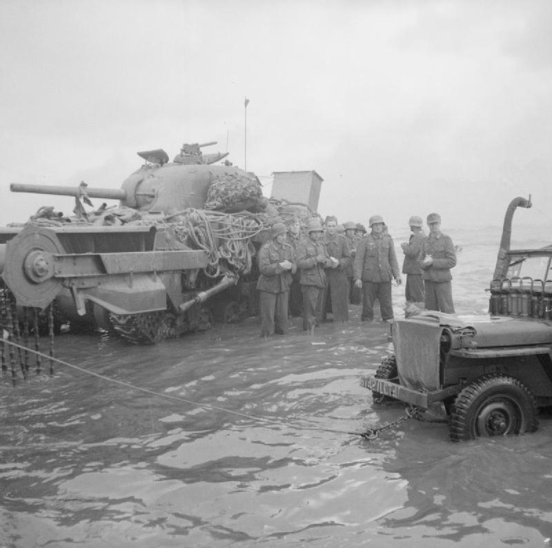 German prisoners, up to their knees in the sea, wait for collection in the shadow of a disabled Sherman Crab flail tank.