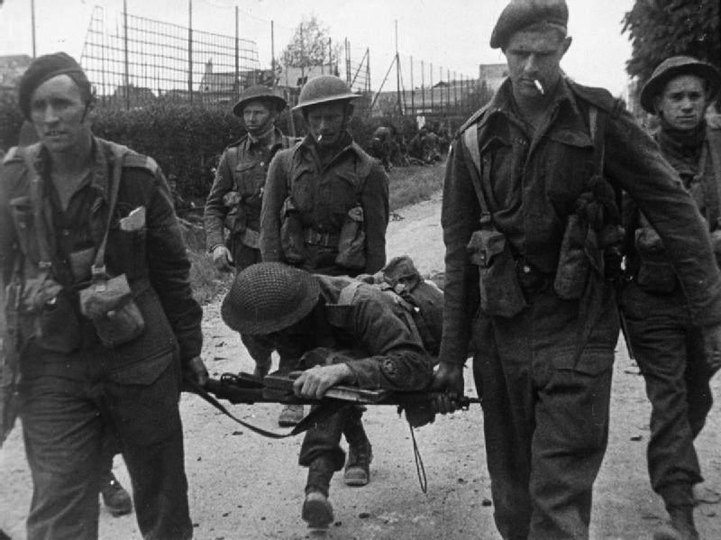A casualty is carried back on an improvised stretcher to a Regimental Aid Post for treatment.