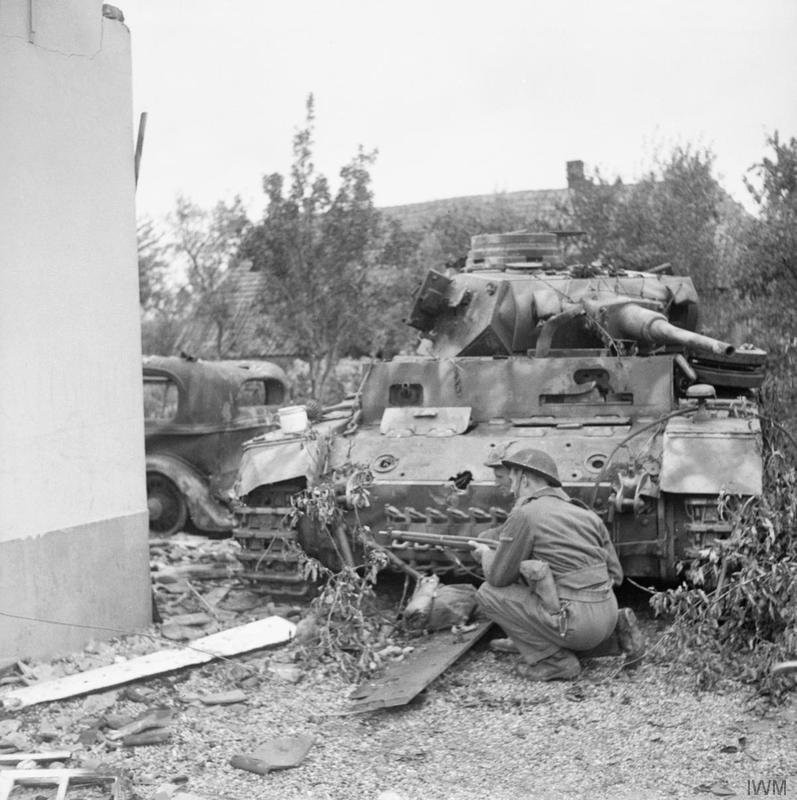 A soldier crouches near a German PzKpfw III tank of Panzer-Kompanie Mielke, Kampfgruppe Knaust (knocked out by No. 1 Squadron, Welsh Guards), in Oosterhout near Nijmegen, 24 September 1944.