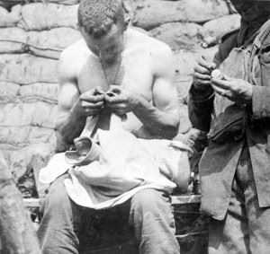 A New Zealand soldier in a trench examining his shirt for lice