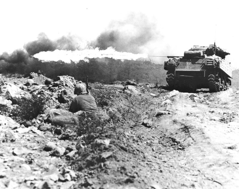 "A Marine flame throwing tank, also known as a ""Ronson"", scorches a Japanese strongpoint."