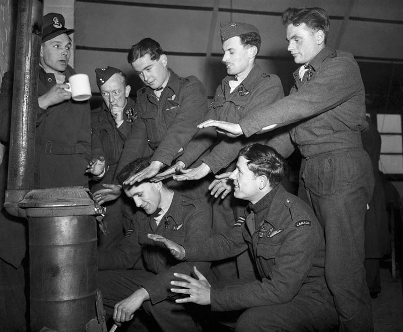 """The crew of Lancaster """"C for Charlie"""" of No 44 Squadron try to warm themselves in their Nissen hut quarters at Dunholme Lodge, after returning from a raid on Stuttgart, 2 March 1944."""