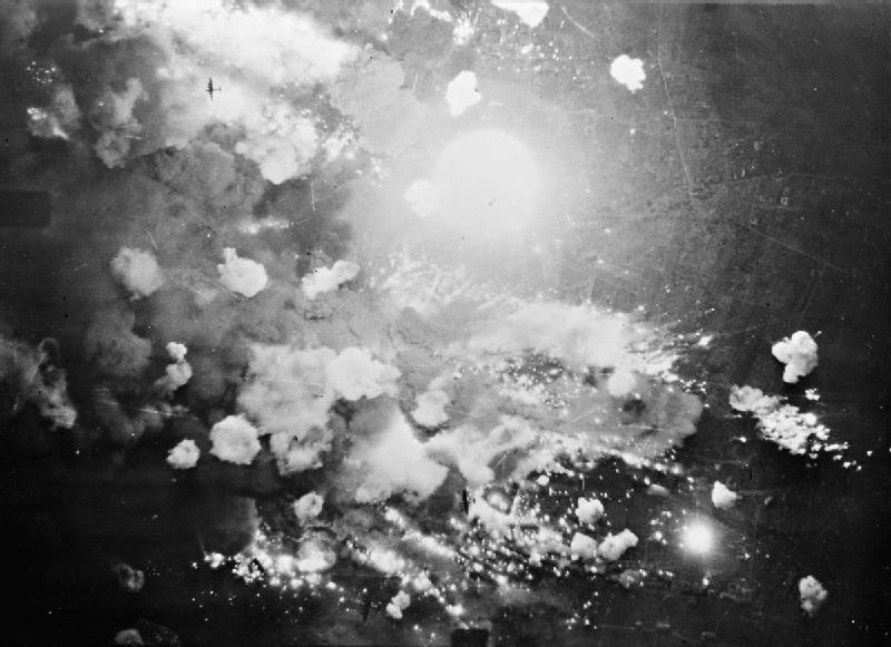 Vertical aerial photograph taken over Pforzheim, Germany, during the first and only area-bombing raid on the city. High explosive and incendiary bombs explode in the target area at the height of the attack. Three Avro Lancasters can be made out; one at upper left and two more at bottom centre, as they overfly the target.