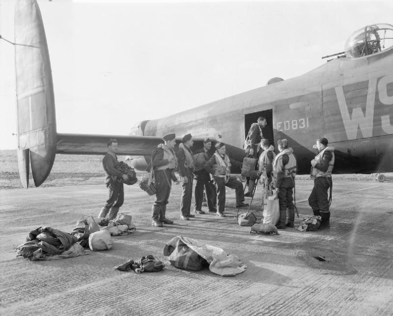 The crew of Avro Lancaster B Mark III, ED831 'WS-H', of No 9 Squadron RAF, captained by Squadron Leader A M Hobbs RNZAF, boarding their aircraft at Bardney, Lincolnshire, for a raid on the Zeppelin works at Friedrichshafen, on the shores of Lake Constance (Bodensee), Germany.