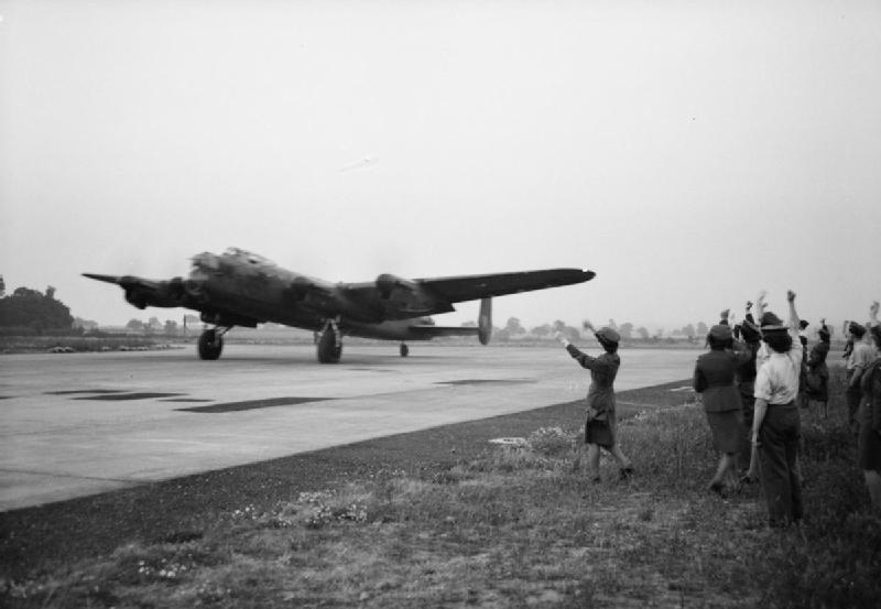 WAAF and other ground crew members wave off Pilot Officer W H Eager RCAF and his crew in Avro Lancaster B Mark I, W4236 'QR-K', of No. 61 Squadron RAF, as they begin their take-off run from Syerston, Nottinghamshire, for a night raid on Hamburg, Germany.