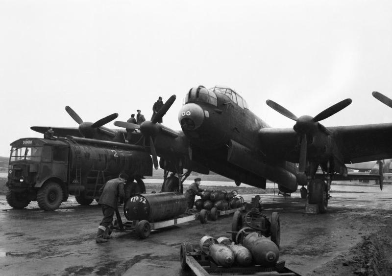 Ground crews refuelling and bombing up an Avro Lancaster of No. 75 (New Zealand) Squadron RAF at Mepal, Cambridgeshire, for a night raid on Krefeld, Germany. The bomb load consists of a 4,000-lb HC 'cookie' and mixed 1,000-lb and 500-lb MC bombs.