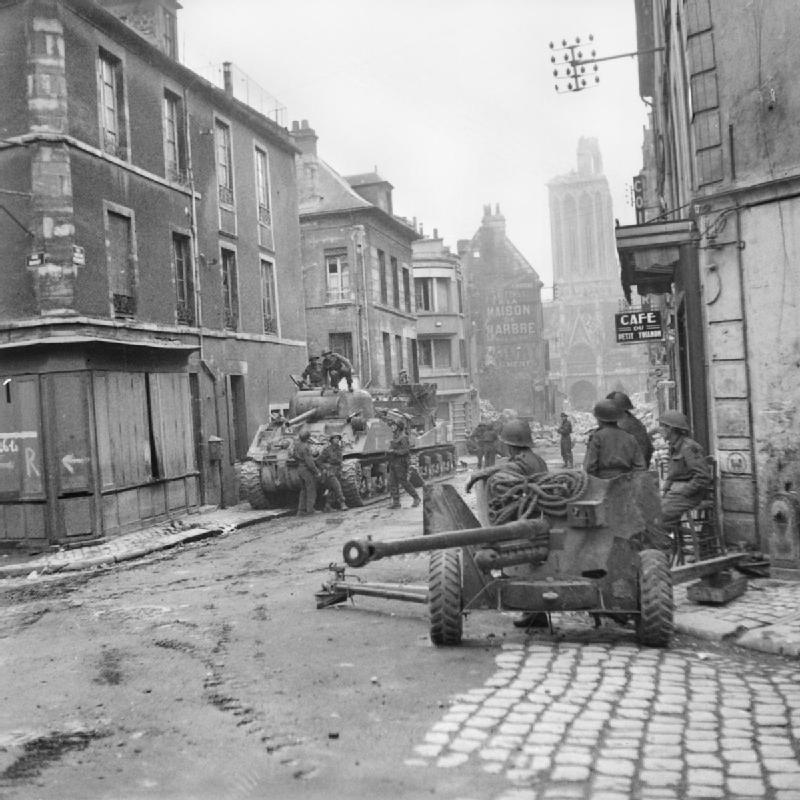 Sherman tanks and 6-pdr anti-tank gun in the centre of Caen, 10 July 1944.