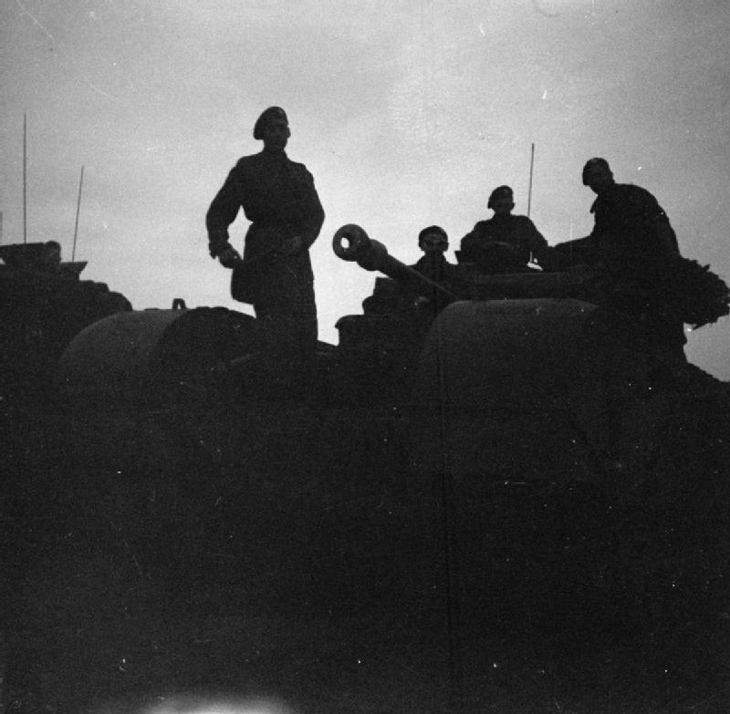 Churchill tanks move up at dawn near the village of Tourville to attack Hill 112, 16 July 1944.