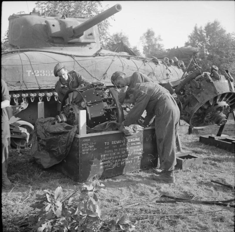 REME fitters prepare to install a new engine into a Sherman tank at 8th Armoured Brigade workshops, 9 August 1944.