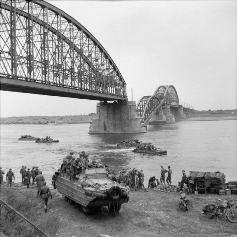 DUKWs transport supplies across the River Waal at Nijmegen, below the railway bridge whose central span was broken by German frogmen using floating mines, 30 September 1944.