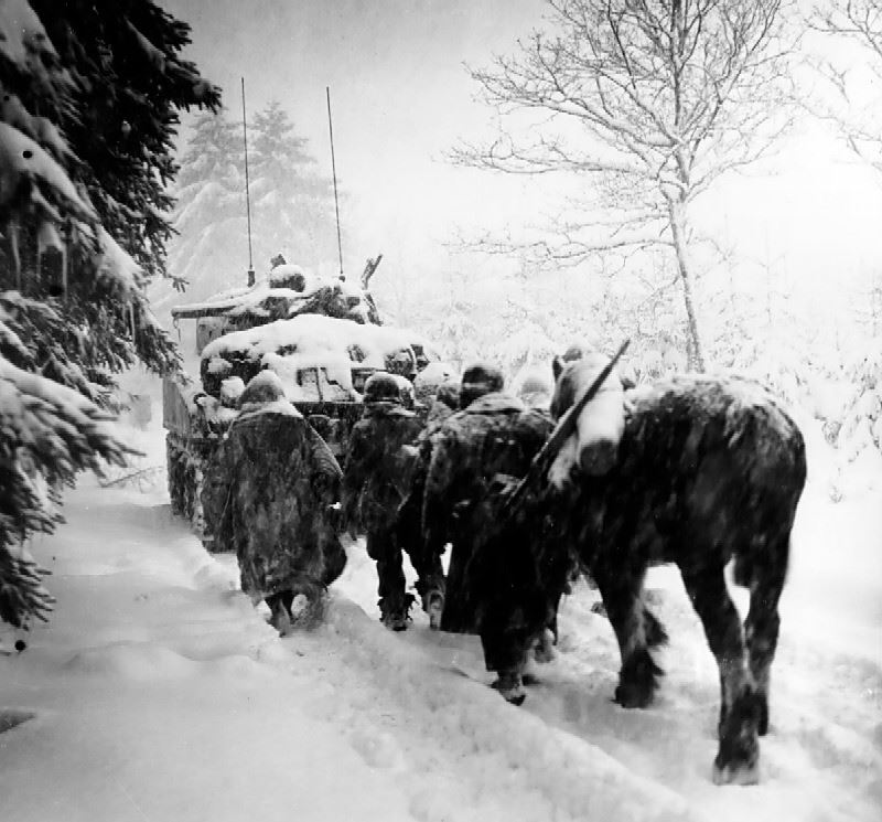 Battle of the bulge - Troops of the 82nd Airborne Division advance in a snowstorm behind the tank in a move to attack Herresbach, Belgium. 340th Tank Battalion,