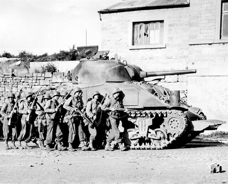 Yanks of 60th Infantry Regiment advance into a Belgian town under the protection of a heavy M4 Sherman tank.