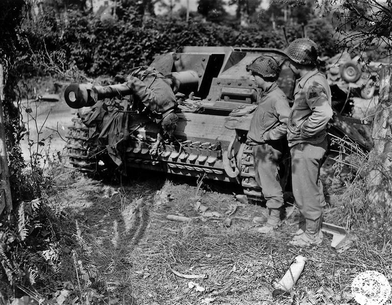 Men of 3rd Armored Division look at the front of a knocked out Sturmgeschütz, the corpse of one of the crew found itself suspended on the end of the barrel of the cannon.