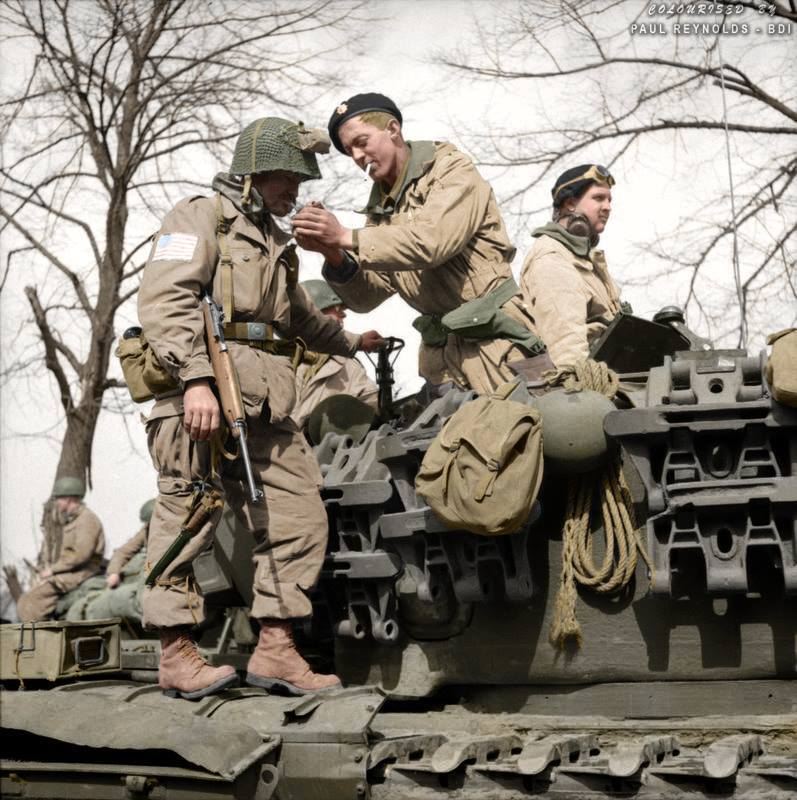 A paratrooper from the American 17th Airborne Division gets a light from a Churchill tank crewman of 6th Guards Armoured Brigade near Dorsten in North Rhine-Westphalia, Germany, 29th of March 1945.
