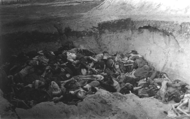More emaciated bodies are piled in one of the many shallow graves that surrounded the camp, located in northern Germany.